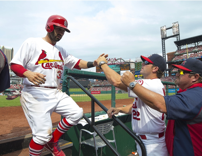 Sep 15, 2013; St. Louis, MO, USA; St. Louis Cardinals second baseman Daniel Descalso (33) is congratulated after scoring a run against the Seattle Mariners at Busch Stadium. The Cardinals defeated the Mariners 12-2. Mandatory Credit: Scott Rovak-USA TODAY Sports