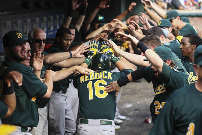 Sep 15, 2013; Arlington, TX, USA; Oakland Athletics right fielder Josh Reddick (16) celebrates with teammates in the dugout after hitting a home run during the ninth inning against the Texas Rangers at Rangers Ballpark in Arlington. Mandatory Credit: Kevin Jairaj-USA TODAY Sports