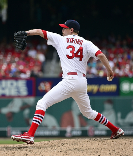 Sep 15, 2013; St. Louis, MO, USA; St. Louis Cardinals relief pitcher John Axford (34) delivers a pitch against the Seattle Mariners during the seventh inning at Busch Stadium. The Cardinals defeated the Mariners 12-2. Mandatory Credit: Scott Rovak-USA TODAY Sports