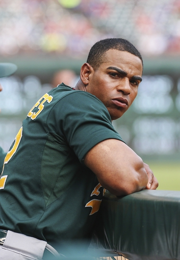 Sep 15, 2013; Arlington, TX, USA; Oakland Athletics designated hitter Yoenis Cespedes (52) looks on from the dugout during the game against the Texas Rangers at Rangers Ballpark in Arlington. Mandatory Credit: Kevin Jairaj-USA TODAY Sports