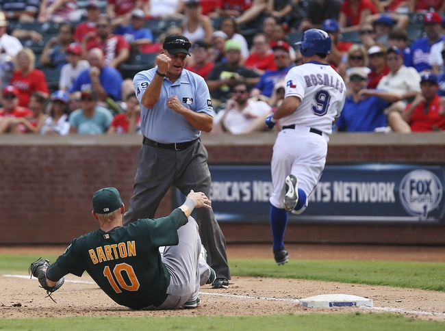 Sep 15, 2013; Arlington, TX, USA; Texas Rangers shortstop Adam Rosales (9) is called out at first base as Oakland Athletics first baseman Daric Barton (10) tumbles to the ground during the eighth inning at Rangers Ballpark in Arlington. Mandatory Credit: Kevin Jairaj-USA TODAY Sports