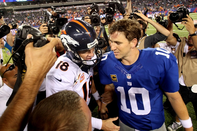 Sep 15, 2013; East Rutherford, NJ, USA; Denver Broncos quarterback Peyton Manning (18) shakes hands with New York Giants quarterback Eli Manning (10) after a game at MetLife Stadium. The Broncos defeated the Giants 41-23. Mandatory Credit: Brad Penner-USA TODAY Sports
