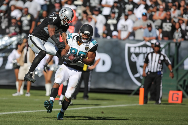Sep 15, 2013; Oakland, CA, USA; Jacksonville Jaguars tight end Clay Harbor (86) catches the ball for a touchdown against Oakland Raiders free safety Charles Woodson (24) during the fourth quarter at O.co Coliseum. The Oakland Raiders defeated the Jacksonville Jaguars 19-9. Mandatory Credit: Kelley L Cox-USA TODAY Sports