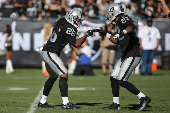 Sep 15, 2013; Oakland, CA, USA; Oakland Raiders free safety Usama Young (26) and cornerback Phillip Adams (28) celebrate after a sack against the Jacksonville Jaguars during the fourth quarter at O.co Coliseum. The Oakland Raiders defeated the Jacksonville Jaguars 19-9. Mandatory Credit: Kelley L Cox-USA TODAY Sports