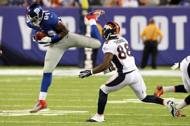 Sep 15, 2013; East Rutherford, NJ, USA; New York Giants tight end Larry Donnell (84) hauls in an on-sides kick in front of Denver Broncos wide receiver Demaryius Thomas (88) during the fourth quarter of a game at MetLife Stadium. The play was ruled illegal touching by Donnell because the ball had not traveled ten yards from the line of scrimmage. The Broncos defeated the Giants 41-23. Mandatory Credit: Brad Penner-USA TODAY Sports