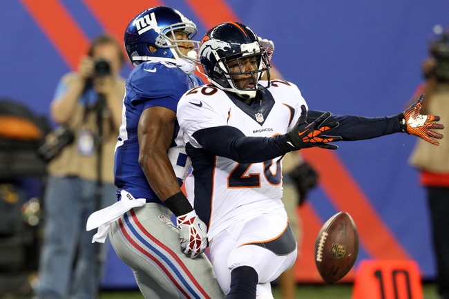 Sep 15, 2013; East Rutherford, NJ, USA; A pass intended for New York Giants wide receiver Victor Cruz (80) is broken up by Denver Broncos safety Mike Adams (20) during the fourth quarter of a game at MetLife Stadium. The Broncos defeated the Giants 41-23. Mandatory Credit: Brad Penner-USA TODAY Sports