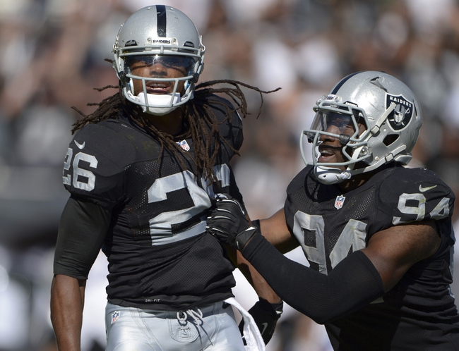 Sep 15, 2013; Oakland, CA, USA; Oakland Raiders safety Usama Young (94) and linebacker Kevin Burnett (94) celebrate after a tackle against the Jacksonville Jaguars at O.co Coliseum. The Raiders defeated the Jaguars 19-9.  Mandatory Credit: Kirby Lee-USA TODAY Sports
