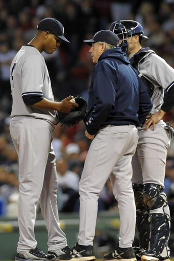 Sep 15, 2013; Boston, MA, USA; New York Yankees pitching coach Larry Rothschild (58) talks with starting pitcher Ivan Nova (47) during the first inning against the Boston Red Sox at Fenway Park. Mandatory Credit: Bob DeChiara-USA TODAY Sports