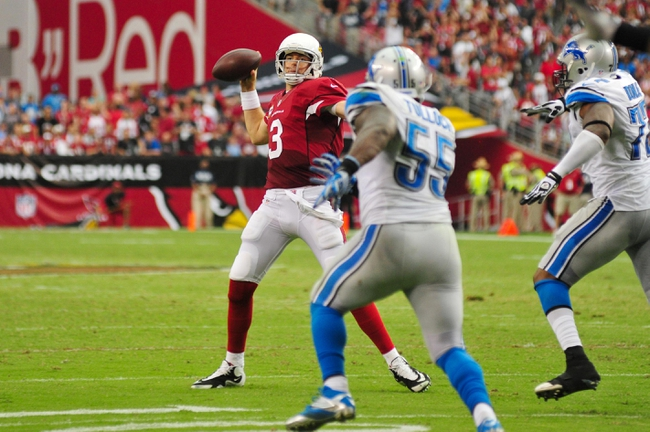 Sep 15, 2013; Phoenix, AZ, USA; Arizona Cardinals quarterback Carson Palmer (3) looks to pass while under pressure from Detroit Lions middle linebacker Stephen Tulloch (55) and defensive end Israel Idonije (77) during the second half at University of Phoenix Stadium. Mandatory Credit: Matt Kartozian-USA TODAY Sports