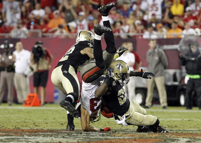 Sep 15, 2013; Tampa, FL, USA; Tampa Bay Buccaneers wide receiver Vincent Jackson (83) flips over New Orleans Saints strong safety Kenny Vaccaro (32) and free safety Malcolm Jenkins (27) after catching the ball during the second half at Raymond James Stadium. The Saints won 16-14. Mandatory Credit: Kim Klement-USA TODAY Sports