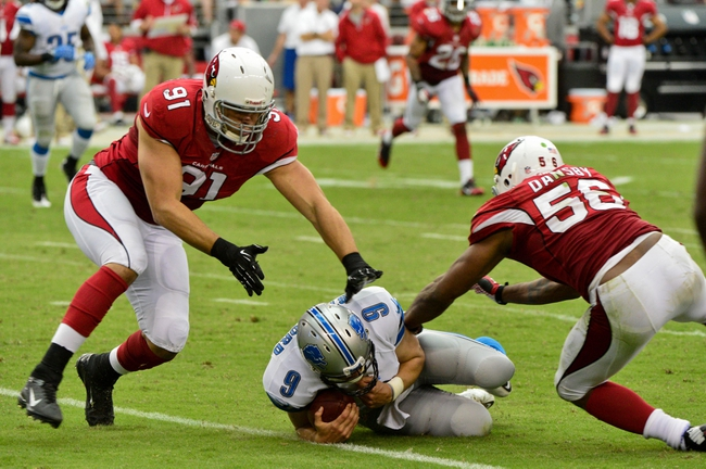 Sep 15, 2013; Phoenix, AZ, USA; Detroit Lions quarterback Matthew Stafford (9) slides as Arizona Cardinals defensive end Matt Shaughnessy (91) and inside linebacker Karlos Dansby (56) defend during the second half at University of Phoenix Stadium. Mandatory Credit: Matt Kartozian-USA TODAY Sports