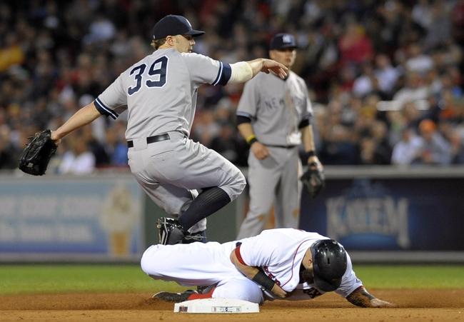 Sep 15, 2013; Boston, MA, USA; Boston Red Sox first baseman Mike Napoli (12) slides into New York Yankees third baseman Mark Reynolds (39) and is forced out during the third inning at Fenway Park. Mandatory Credit: Bob DeChiara-USA TODAY Sports