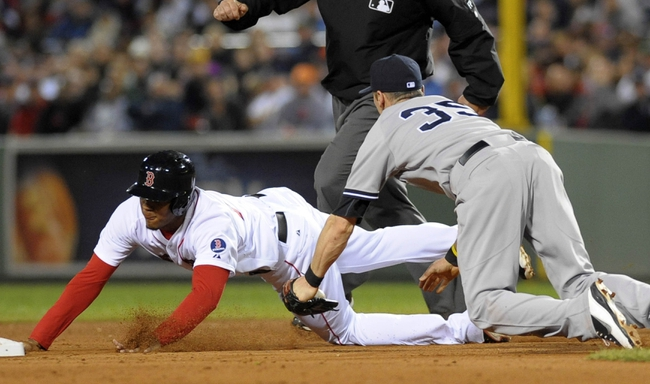 Sep 15, 2013; Boston, MA, USA; Boston Red Sox third baseman Xander Bogaerts (left) slides past the tag of New York Yankees shortstop Brendan Ryan (35) during the fourth inning at Fenway Park. Mandatory Credit: Bob DeChiara-USA TODAY Sports