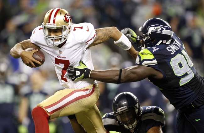 Sep 15, 2013; Seattle, WA, USA; San Francisco 49ers quarterback Colin Kaepernick (7) is tackled by Seattle Seahawks defensive tackle D'Anthony Smith (94) and outside linebacker K.J. Wright (50) during the fourth quarter at CenturyLink Field. Mandatory Credit: Joe Nicholson-USA TODAY Sports