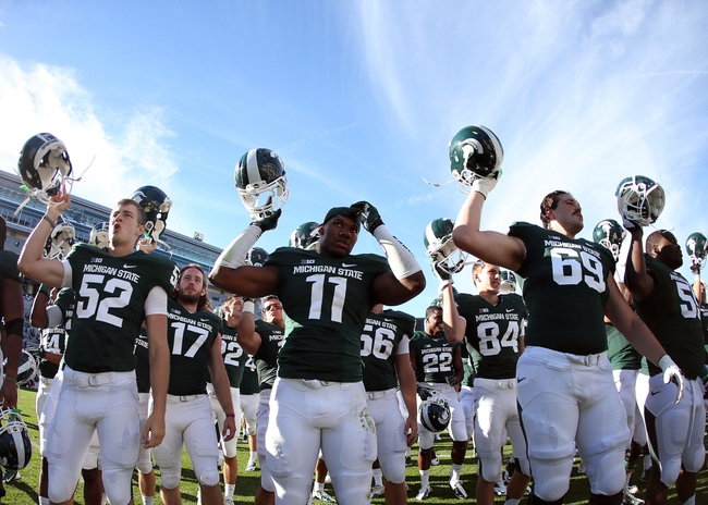 Sep 14, 2013; East Lansing, MI, USA; Michigan State Spartans long snapper Taybor Pepper (52) and defensive end Jamal Lyles (11) and offensive tackle Shawn Kamm (69) celebrate a win after a game between the Michigan State Spartans and the Youngstown State Penguins at Spartan Stadium. Mandatory Credit: Mike Carter-USA TODAY Sports