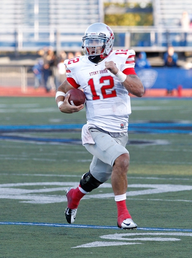 Sep 14, 2013; Buffalo, NY, USA; Stony Brook Seawolves quarterback Lyle Negron (12) runs with the ball during the game against the Buffalo Bulls at University of Buffalo Stadium. Buffalo beats Stony Brook 26-23 in OT. Mandatory Credit: Kevin Hoffman-USA TODAY Sports