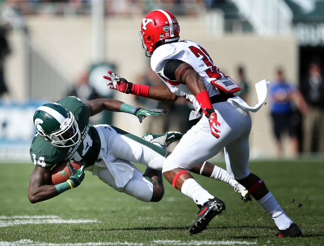 Sep 14, 2013; East Lansing, MI, USA; Michigan State Spartans wide receiver Tony Lippett (14) is tripped up by Youngstown State Penguins safety Tre' Moore (30) during the second half in a game at Spartan Stadium. MSU won 55-17.Mandatory Credit: Mike Carter-USA TODAY Sports