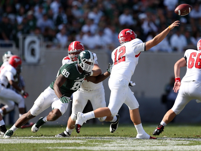 Sep 14, 2013; East Lansing, MI, USA; Youngstown State Penguins quarterback Kurt Hess (12) passes against Michigan State Spartans defensive end Shilique Calhoun (89) during the second half in a game at Spartan Stadium. MSU won 55-17.Mandatory Credit: Mike Carter-USA TODAY Sports