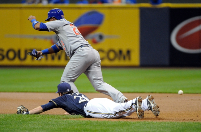 Sep 16, 2013; Milwaukee, WI, USA;  Milwaukee Brewers first baseman Jonathan Lucroy (bottom) cannot get to a hit by Chicago Cubs first baseman Anthony Rizzo (not pictured) as third baseman Luis Valbuena (top) advances to 2nd base in the 1st inning at Miller Park. Mandatory Credit: Benny Sieu-USA TODAY Sports