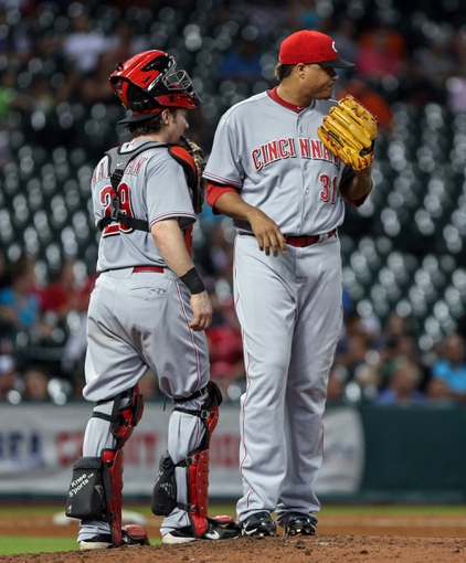 Sep 16, 2013; Houston, TX, USA; Cincinnati Reds catcher Ryan Hanigan (29) talks to relief pitcher Alfredo Simon (31) on the mound during the sixth inning against the Houston Astros at Minute Maid Park. Mandatory Credit: Troy Taormina-USA TODAY Sports