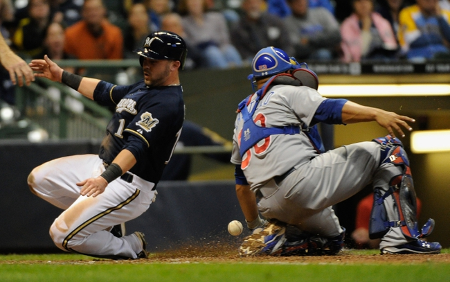 Sep 16, 2013; Milwaukee, WI, USA; Milwaukee Brewers left fielder Caleb Gindl (left) scores on a base hit by first baseman Yuniesky Betancourt (not pictured) as the ball gets by Chicago Cubs catcher Welington Castillo (right) in the sixth inning at Miller Park. Mandatory Credit: Benny Sieu-USA TODAY Sports
