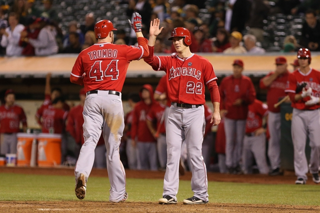 Sep 16, 2013; Oakland, CA, USA; Los Angeles Angels first baseman Mark Trumbo (44) high fives catcher John Hester (22) at the plate after batting him in on a two run home run against the Oakland Athletics during the eighth inning at O.co Coliseum. Mandatory Credit: Kelley L Cox-USA TODAY Sports