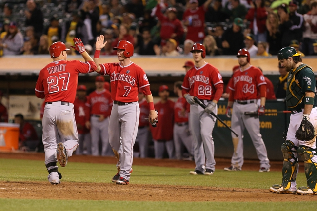 Sep 16, 2013; Oakland, CA, USA; Los Angeles Angels center fielder Mike Trout (27) high fives third baseman Andrew Romine (7) at the plate after batting him in on a two run home run against the Oakland Athletics during the eighth inning at O.co Coliseum. Mandatory Credit: Kelley L Cox-USA TODAY Sports