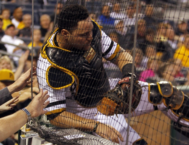 Sep 17, 2013; Pittsburgh, PA, USA; Pittsburgh Pirates catcher Russell Martin (55) gets tangled in the net behind home plate after catching a foul ball by San Diego Padres catcher Nick Hundley (not pictured) during the second inning at PNC Park. Mandatory Credit: Charles LeClaire-USA TODAY Sports