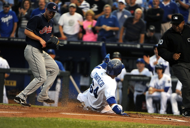 Sep 17, 2013; Kansas City, MO, USA; Kansas City Royals second baseman Emilio Bonifacio (64) scores in the first inning as Cleveland Indians starting pitcher Corey Kluber (28) covers home plate at Kauffman Stadium. Mandatory Credit: John Rieger-USA TODAY Sports
