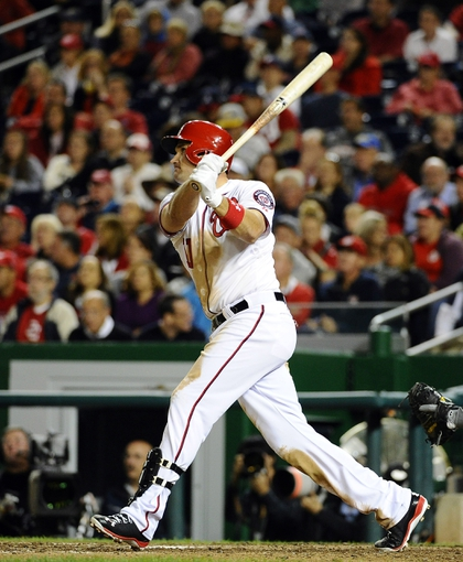 Sep 17, 2013; Washington, DC, USA; Washington Nationals third baseman Ryan Zimmerman (11) hits a solo home run against the Atlanta Braves during the eighth inning at Nationals Park. The Nationals won 4 - 0. Mandatory Credit: Brad Mills-USA TODAY Sports