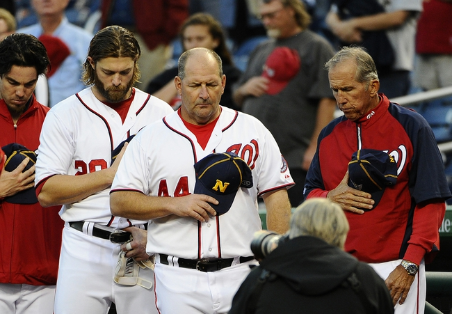 Sep 17, 2013; Washington, DC, USA; Washington Nationals right fielder Jayson Werth (28) and coach Trent Jewett (center) and manager Davey Johnson (right) observe a moment of silence before the game against the Atlanta Braves in remembrance of those who lost their lives Monday at the nearby Washington Navy Yard at Nationals Park. Mandatory Credit: Brad Mills-USA TODAY Sports