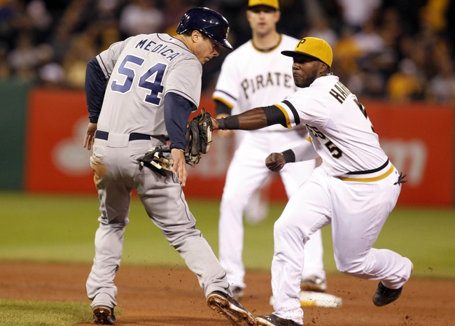 Sep 17, 2013; Pittsburgh, PA, USA; San Diego Padres first baseman Tommy Medica (54) is tagged out on the front end of a double play by Pittsburgh Pirates second baseman Josh Harrison (5) during the seventh inning at PNC Park. The San Diego Padres won 5-2. Mandatory Credit: Charles LeClaire-USA TODAY Sports