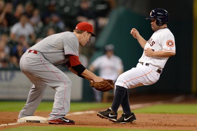 Sep 17, 2013; Houston, TX, USA; Houston Astros second baseman Jose Altuve (27) avoids a tag by Cincinnati Reds third baseman Todd Frazier (21) during the first inning at Minute Maid Park. Mandatory Credit: Thomas Campbell-USA TODAY Sports