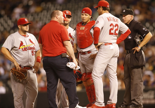 Sep 17, 2013; Denver, CO, USA; Members of the St. Louis Cardinals including manager Mike Matheny (22), catcher Yadier Molina (4), first baseman Matt Adams (53) and a team trainer talk to starting pitcher Joe Kelly (58) during the fifth inning against the Colorado Rockies at Coors Field. Mandatory Credit: Chris Humphreys-USA TODAY Sports