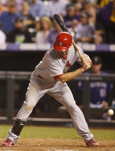Sep 17, 2013; Denver, CO, USA; St. Louis Cardinals second baseman Matt Carpenter (13) is hit by a pitch during the fifth inning against the Colorado Rockies at Coors Field. Mandatory Credit: Chris Humphreys-USA TODAY Sports