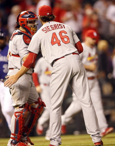 Sep 17, 2013; Denver, CO, USA; St. Louis Cardinals pitcher Kevin Siegrist (46) celebrates with catcher Yadier Molina (4) after the game against the Colorado Rockies at Coors Field. The Cardinals won 11-4.  Mandatory Credit: Chris Humphreys-USA TODAY Sports