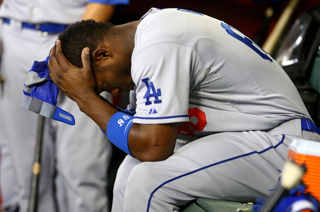 Sept. 17, 2013; Phoenix, AZ, USA: Los Angeles Dodgers outfielder Yasiel Puig reacts in the dugout in the eighth inning against the Arizona Diamondbacks at Chase Field. Mandatory Credit: Mark J. Rebilas-USA TODAY Sports
