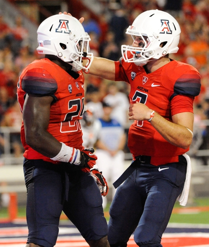 Sep 14, 2013; Tucson, AZ, USA; Arizona Wildcats running back KaDeem Carey (25) is congratulated by quarterback B.J. Denker (7) after scoring a touchdown that was later called back because of an illegal formation during the fourth quarter against the Texas-San Antonio Roadrunners at Arizona Stadium. The Wildcats defeated the Roadrunners 38-13. Mandatory Credit: Casey Sapio-USA TODAY Sports