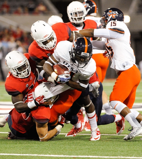 Sep 14, 2013; Tucson, AZ, USA; Texas-San Antonio Roadrunners wide receiver Kenny Bias (81) is tackled by Arizona Wildcats safety Jared Tevis (38) safety Wayne Capers Jr. (12) and safety William Parks (11) during the fourht quarter at Arizona Stadium. The Wildcats defeated the Roadrunners 38-13. Mandatory Credit: Casey Sapio-USA TODAY Sports
