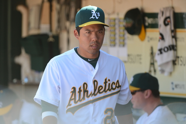 September 18, 2013; Oakland, CA, USA; Oakland Athletics catcher Kurt Suzuki (22) stands in the dugout against the Los Angeles Angels during the 10th inning at O.co Coliseum. The Angels defeated the Athletics 5-4 in 11 innings. Mandatory Credit: Kyle Terada-USA TODAY Sports