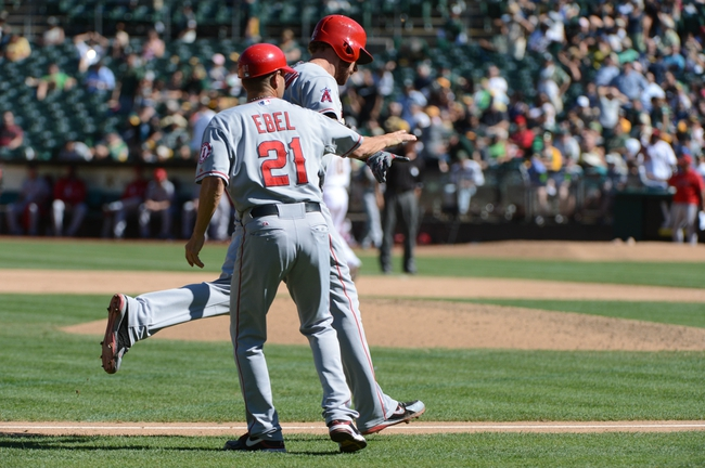 September 18, 2013; Oakland, CA, USA; Los Angeles Angels designated hitter Josh Hamilton (32, back) is congratulated by third base coach Dino Ebel (21) after hitting a two-run home run against the Oakland Athletics during the ninth inning at O.co Coliseum. The Angels defeated the Athletics 5-4 in 11 innings. Mandatory Credit: Kyle Terada-USA TODAY Sports