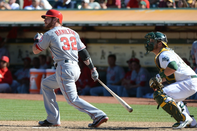 September 18, 2013; Oakland, CA, USA; Los Angeles Angels designated hitter Josh Hamilton (32) hits a sacrifice fly to score left fielder J.B. Shuck (39, not pictured) against Oakland Athletics catcher Stephen Vogt (21, right) during the 11th inning at O.co Coliseum. The Angels defeated the Athletics 5-4 in 11 innings. Mandatory Credit: Kyle Terada-USA TODAY Sports