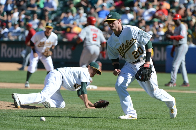 September 18, 2013; Oakland, CA, USA; Oakland Athletics third baseman Josh Donaldson (20) makes a fielding error on a bunt by Los Angeles Angels shortstop Erick Aybar (2) during the 11th inning at O.co Coliseum. The Angels defeated the Athletics 5-4 in 11 innings. Mandatory Credit: Kyle Terada-USA TODAY Sports
