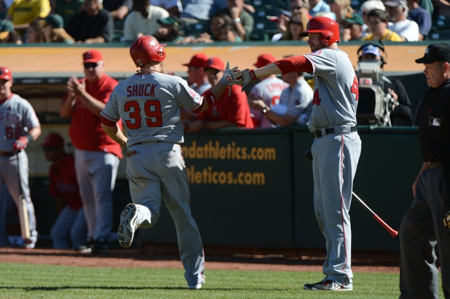 September 18, 2013; Oakland, CA, USA; Los Angeles Angels left fielder J.B. Shuck (39) is congratulated by first baseman Mark Trumbo (44) for scoring on a sacrifice fly by designated hitter Josh Hamilton (32, not pictured) against the Oakland Athletics during the 11th inning at O.co Coliseum. The Angels defeated the Athletics 5-4 in 11 innings. Mandatory Credit: Kyle Terada-USA TODAY Sports