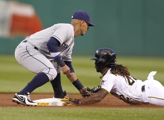 Sep 18, 2013; Pittsburgh, PA, USA; San Diego Padres shortstop Ronny Cedeno (left) applies an out tag as Pittsburgh Pirates center fielder Andrew McCutchen (22) is caught attempting to steal second base during the first inning at PNC Park. Mandatory Credit: Charles LeClaire-USA TODAY Sports
