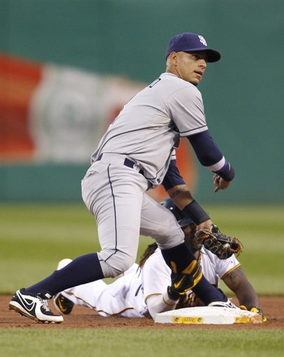 Sep 18, 2013; Pittsburgh, PA, USA; San Diego Padres shortstop Ronny Cedeno (left) gestures as Pittsburgh Pirates center fielder Andrew McCutchen (bottom) is caught attempting to steal second base during the first inning at PNC Park. Mandatory Credit: Charles LeClaire-USA TODAY Sports