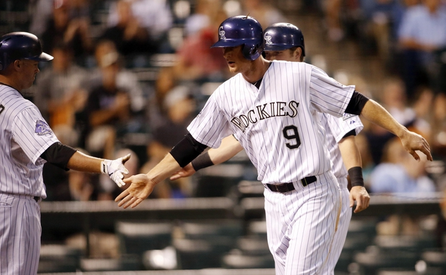 Sep 18, 2013; Denver, CO, USA; Colorado Rockies third baseman DJ LeMahieu (9) greets teammates after scoring during the first inning against the St. Louis Cardinals at Coors Field. Mandatory Credit: Chris Humphreys-USA TODAY Sports