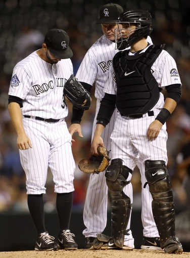 Sep 18, 2013; Denver, CO, USA; Colorado Rockies pitcher Tyler Chatwood (32) talks with pitching coach Jim Wright (center) and catcher Jordan Pacheco (right) during the third inning against the St. Louis Cardinals at Coors Field. Mandatory Credit: Chris Humphreys-USA TODAY Sports
