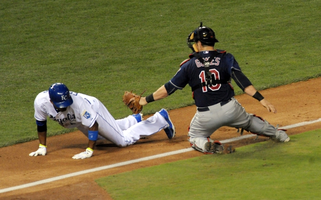 Sep 18, 2013; Kansas City, MO, USA; Cleveland Indians catcher Yan Gomes (10) misses the tag on Kansas City Royals shortstop Alcides Escobar (2) in the fifth inning at Kauffman Stadium. Mandatory Credit: Denny Medley-USA TODAY Sports