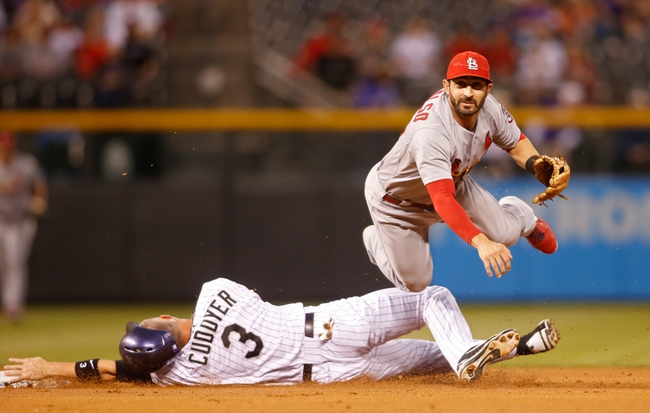 Sep 18, 2013; Denver, CO, USA; St. Louis Cardinals shortstop Daniel Descalso (33) turns a double play during the first inning against the Colorado Rockies at Coors Field. Mandatory Credit: Chris Humphreys-USA TODAY Sports